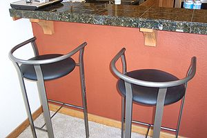 Two bar stool in front of a kitchen counter