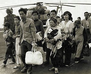 South Vietnamese refugees walk across a U.S. N...