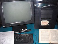 """Black equipment on a teal blue desk. At left a monitor and at right a cube, both with small NeXT logos and in front a keyboard that says """"Propriete CERN"""". Resting on the keyboard is a copy of """"Information Management: A Proposal"""", and to its right is a book, probably """"Enquire Within upon Everything"""". A partly peeled off label on the cube says, """"This machine is a server. DO NOT POWER IT DOWN!!"""""""