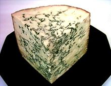 A corner of cheese with greenish streaks through it