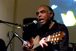 Gilberto Gil singing with guitar.