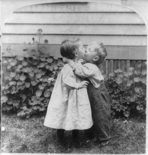 Two small children kissing.