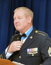 Head and shoulders of a blond-haired white man in military uniform, standing before a microphone. His right hand is touching a medal hanging from a light blue ribbon around his neck.