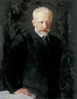 A middle-aged man with grey hair and a beard, wearing a dark suit and staring intently at the viewer.