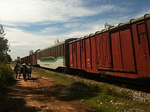 English: A northbound train passes next to a c...