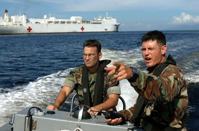 US Navy 070922-N-0194K-536 Lt.j.g. Mike Porfirio, left, and Master-at-Arms 3rd Class Pablo Ordonez conduct a security patrol in the waters around Military Sealift Command hospital ship USNS Comfort (T-AH 20)