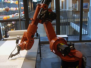 An industrial robot, which writes down the bib...