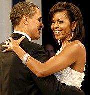 Barack en Michelle Obama dans arm-in-arm en Glimlach.  Ze Draagt Een witte jurk, Grote ring, lange oorbellen en Een armband.  HIJ Draagt Een zwarte roken.
