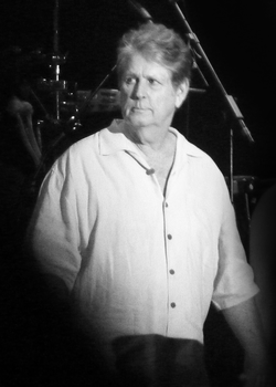 Black and white photograph of Wilson standing onstage looking out to the audience. He is wearing a casual long-sleeved shirt.