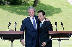 President George W. Bush embraces South Korean...