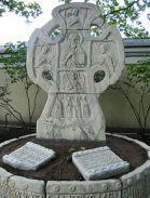 A large stone Russian cross with a figure carved on it, behind two stone tablets set into the ground