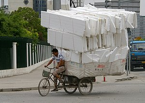 A man is riding a tricycle with heavy load on ...