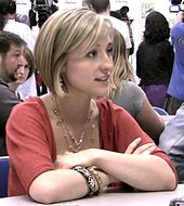 Jonge, blonde vrouw met de armen dan Elkaar aan Een tafel
