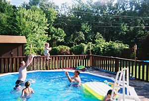 English: a baby in the air above a swimming po...