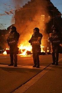 English: Policemen in riot control gear operat...