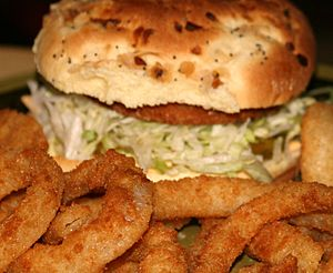 Chicken sandwich on an onion roll served with ...