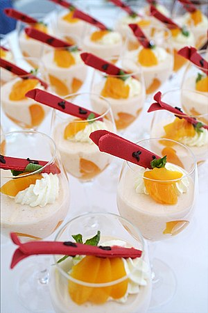 Mousse decorated with peaches, whipped cream, ...