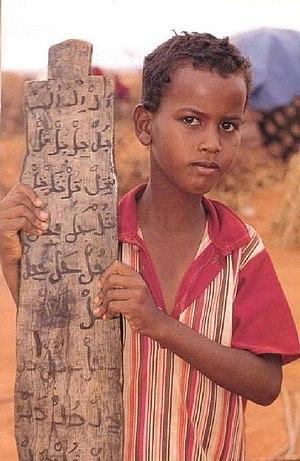 English: Somali boy holding up a Qur'anic pray...