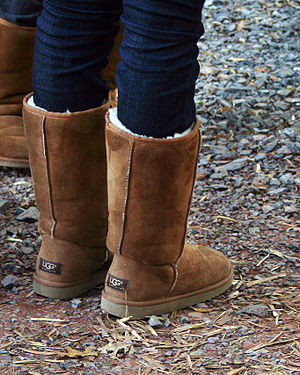 Pair of chestnut Ugg boots with jeans tucked i...