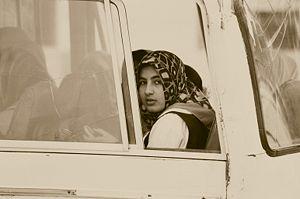 Iraqi girl looks out the window of a school bu...