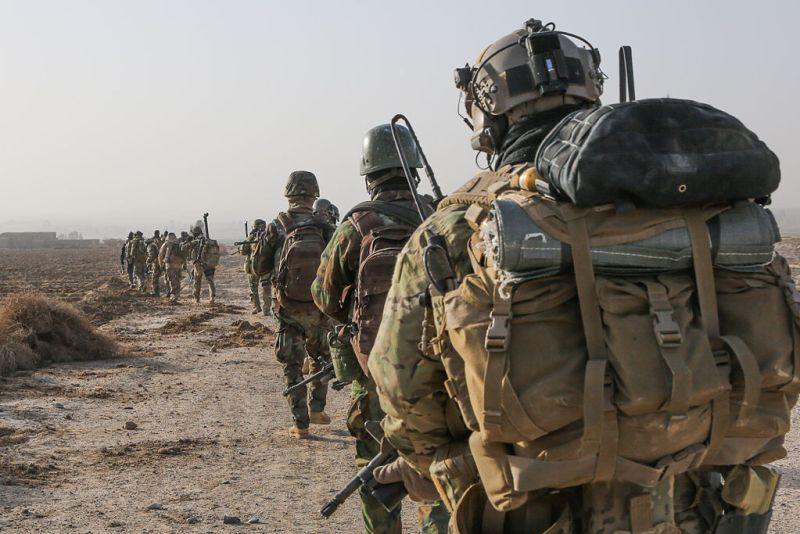 A U.S. Army Special Forces Soldier with Combined Joint Special Operations Task Force-Afghanistan and Afghan National Army commandos with the 3rd Company, 3rd Special Operations Kandak move toward a compound