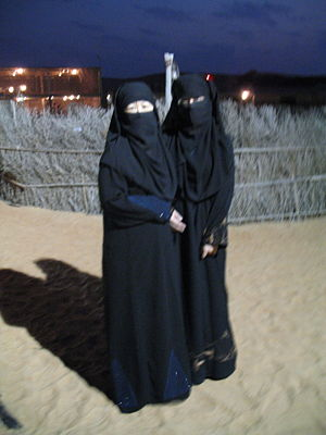 Two women dressed in abayas.