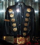 Sebuah jaket hitam dengan lima putaran medali  emas di sebelah  kiri dan bahu kanan dan larangan emas di lengan tangan  kirinya. Jaket  itu memiliki tali sabuk dua di lengan kanan bawah. Di  bawah jaket  adalah sabuk emas, dengan liontin bulat di tengahnya. Ada  lampu merah  merefleksikan jaket dan sabuk serta plat kuadrat emas di  sisi kiri  jaket dan sabuk.