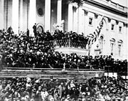 A large crowd in front of a large building with many pillars.