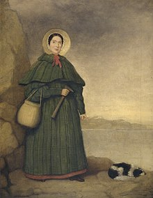 Portrait of a woman in bonnet and long dress holding rock hammer, pointing at fossil next to spaniel dog lying on ground.