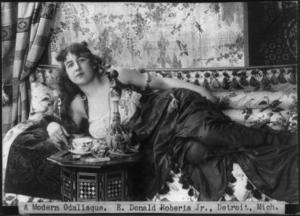 Glamorous woman reclining on sofa.