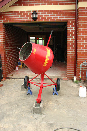 A portable cement mixer in action. It has whee...