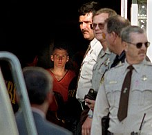 McVeigh is located at the center of the image in a dark hallway wearing an orange jumpsuit and looking to the side. Around him are several FBI agents and police officers.