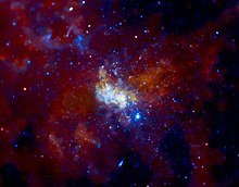 A white, glowing, cloudlike feature lies surrounded by bright blue stars in a brownish, golden nebula