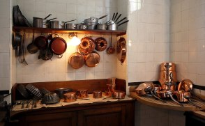 a shelf with kitchen utensils of several kinds stacked upon it, with more utensils hanging from hooks below it, both above two work surfaces with yet further utensils laid out neatly upon them