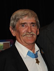 Head and shoulders of a white man with a pointed mustache, wearing a star-shaped medal on a blue ribbon around his neck.