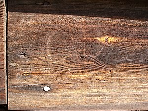 Scratched wooden plank of house facade.