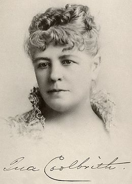 "A fine charcoal portrait of Ina Coolbrith in her 30s or 40s, shown from the neck up, wearing a garment with a high, open collar made of lace, with hair curled and secured atop the head, looking slightly to the left. A fountain pen signature is below the portrait, reading ""Ina Coolbrith"", the letter ""c"" writ large to sweep underneath the next five letters."