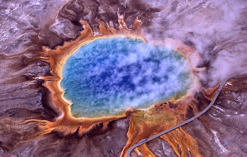 Aerial view of Grand Prismatic Spring, Wikimedia photo (all text in caption from Wikimedia); Hot Springs, Midway & Lower Geyser Basin, Yellowstone National Park. The spring is approximately 250 by 300 feet (75 by 91 m) in size.  This photo shows steam rising from hot and sterile deep azure blue water (owing to the light absorbing overtone of an OH stretch which is shifted to 698 nm by hydrogen bonding [1]) in the center surrounded by huge mats of brilliant orange algae and bacteria. The color of which is due to the ratio of chlorophyll to carotenoid molecules produced by the organisms. During summertime the chlorophyll content of the organisms is low and thus the mats appear orange, red, or yellow. However during the winter, the mats are usually dark green, because sunlight is more scarce and the microbes produce more chlorophyll to compensate, thereby masking the carotenoid colors.