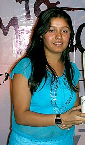 Sunidhi Chauhan smiling wearing a blue top