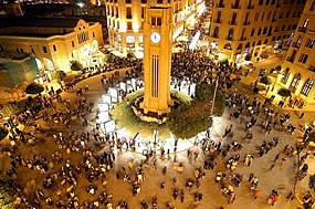 Bird's-eye view of people gathering around a clocktower at the center of a street light-lit square at night.