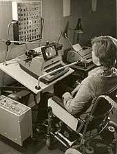 a black and white photograph showing a user sitting in front of a modified typewrite, there is  grid of letters above the typewriter that appear to be lighting up in sequence, a tube goes from the users mouth to the machine