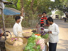 A road-side vegetable-seller weighs goods while two customers check the vegetables.
