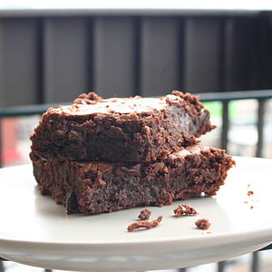 Brownie with crumbs on plate.