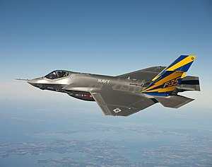 Gray fighter aircraft soars in a clear blue sky with sea coast below.