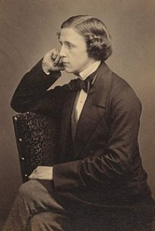 tinted monochrome 3/4-length photo portrait of seated Dodgson holding a book