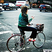 A woman reading SMS messages on her mobile phone while standing on a bike in traffic.