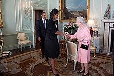 Michelle Obama en Elizabeth II schudden Elkaar de kant en lachen naar Elkaar als Barack Komt de kamer op de Achtergrond.