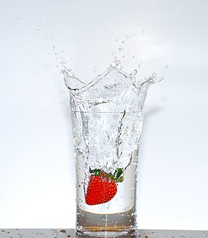 A strawberry falling into a glass of water.