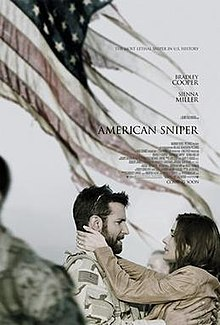 Chris Kyle is wearing desert fatigues army outfit, his wife Taya embraces him. They are standing in front of a tattered US flag.