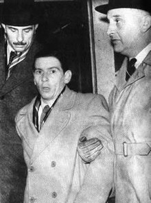 Man being escorted by two taller men on either side of him